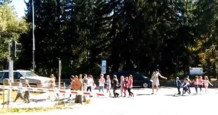 Учителка превежда група деца през жп прелез при спуснати бариери