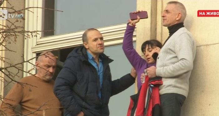 Протестираща медицинска сестра застана на перваза на сградата на парламента